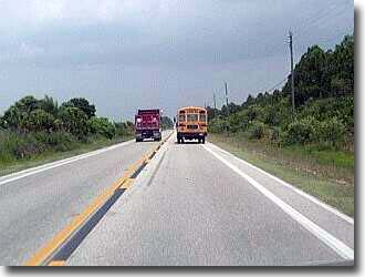 Dump truck blows past schoolbus.
